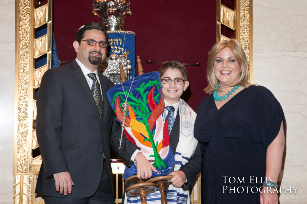 Young Bar Mitzvah poses with his parents while he holds the Torah, at Temple de Hirsch Sinai in Seattle