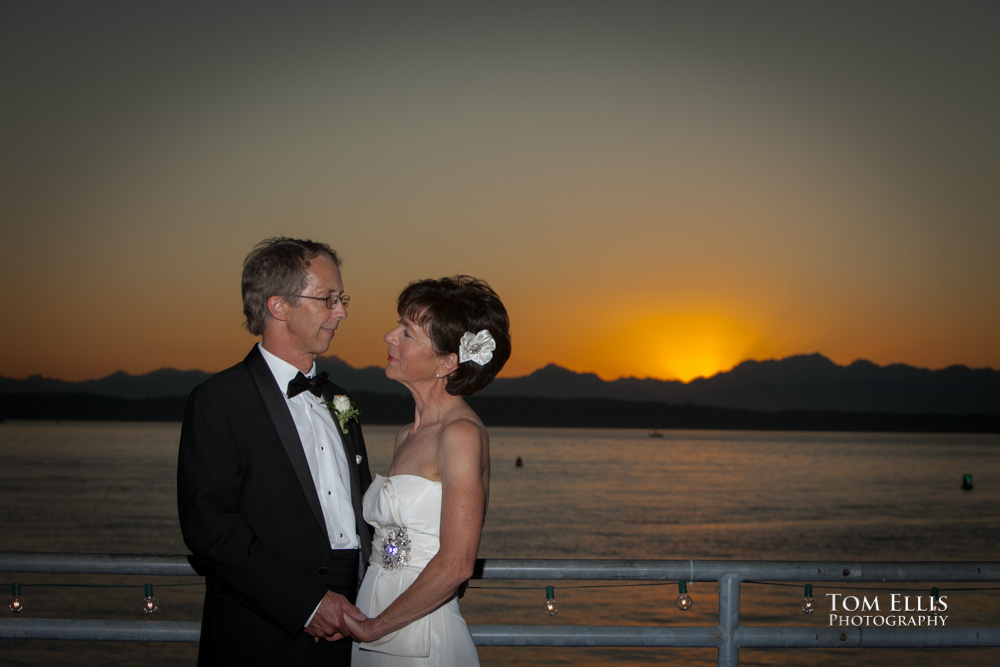 Bride and groom photographed against a background of the sun setting behind the Olympic Mountains during their Seattle area wedding at Ray's Boathouse