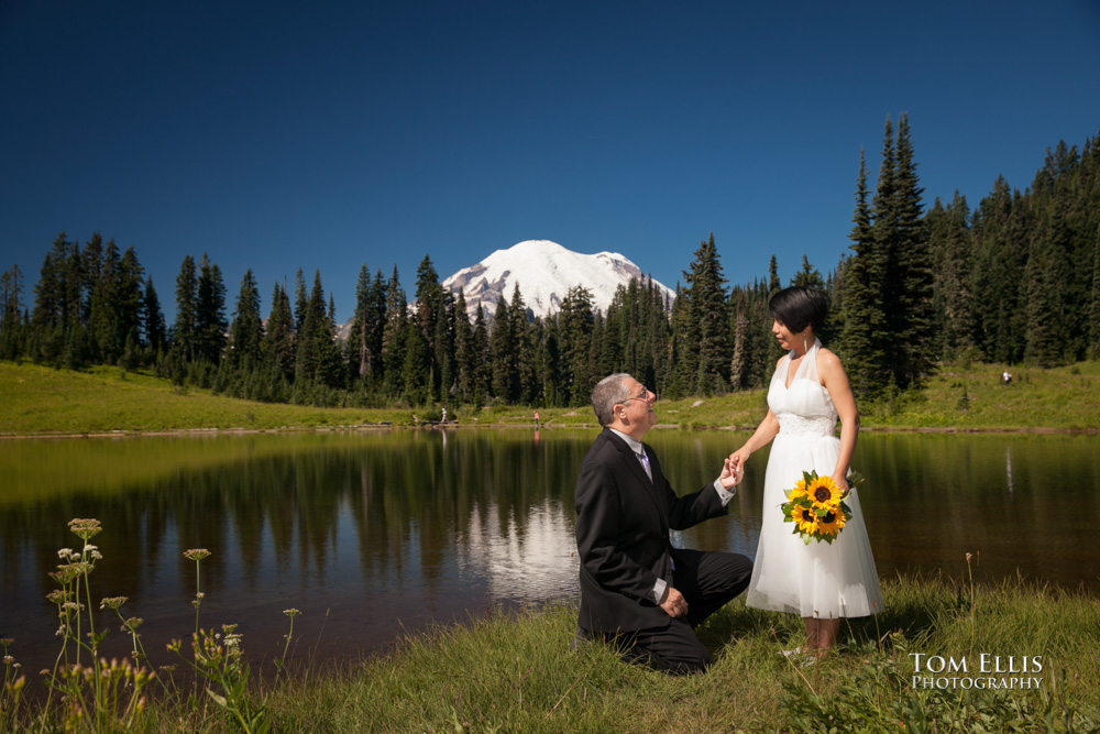 Marty kneels in front of his new wife Pat at Tipsoo Lake with Mt Rainier in the background