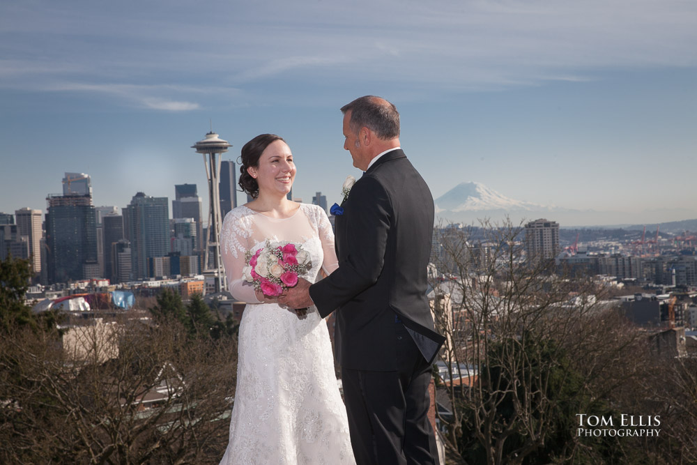 Bride and groom pose at Kerry Park in Seattle, with backdrop of the Space Needle and Mt Rainier