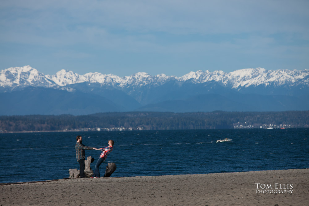 Couple dancing on beach during their engagement photo session, with the Olympic Mountains in the background