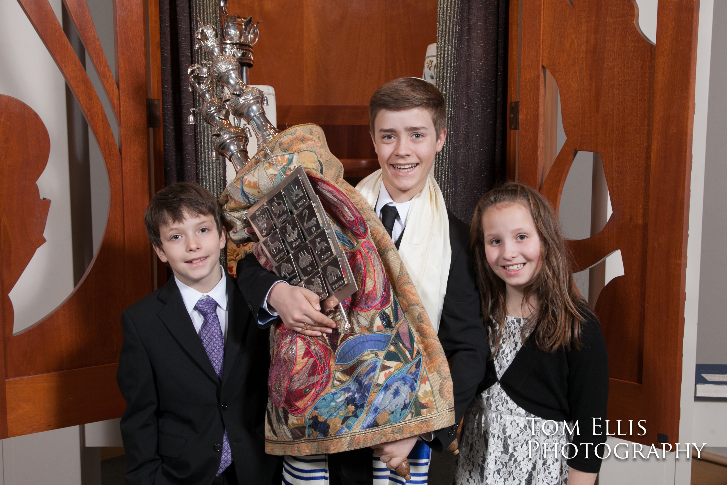 Bar Mitzvah Sam holds the torah, accompanied by younger brother and sister Sam and Isabel