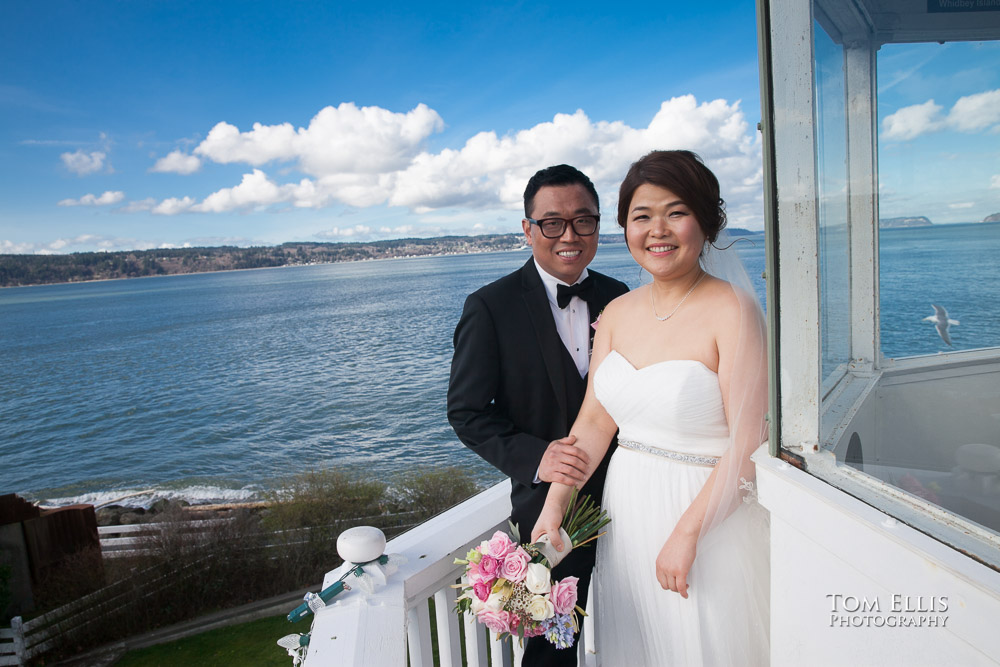 Bride and groom stand on the catwalk at the top of the Mukilteo Lighthouse