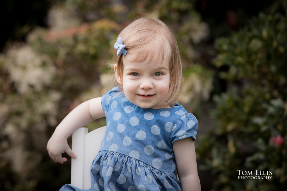 Seattle area family photo session with 18 month old Emily, as she poses in front of her house