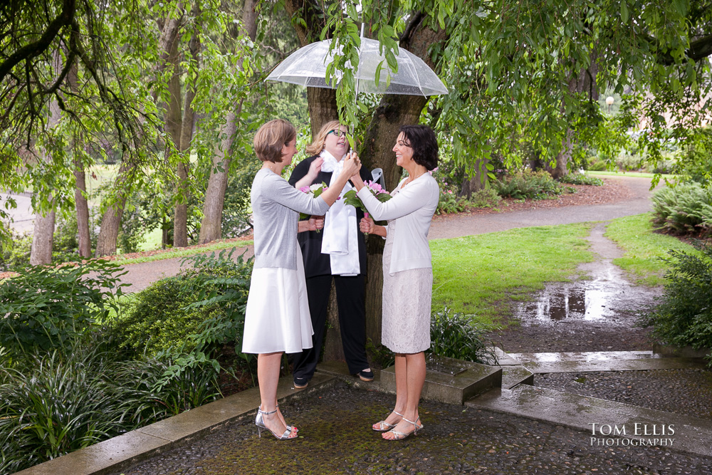 Lesbian couple standing under an umbrella as they exchange their wedding vows on a rainy day in Seattle