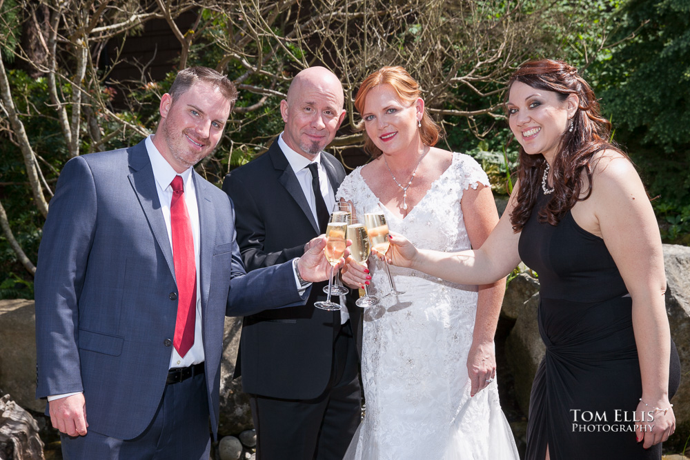 Bride and groom raise their glasses is a toast with the best man and maid of honor