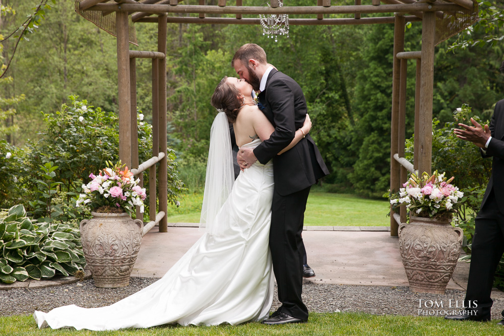 Bride and groom kiss at the conclusion of the wedding ceremony at an outdoor garden venue