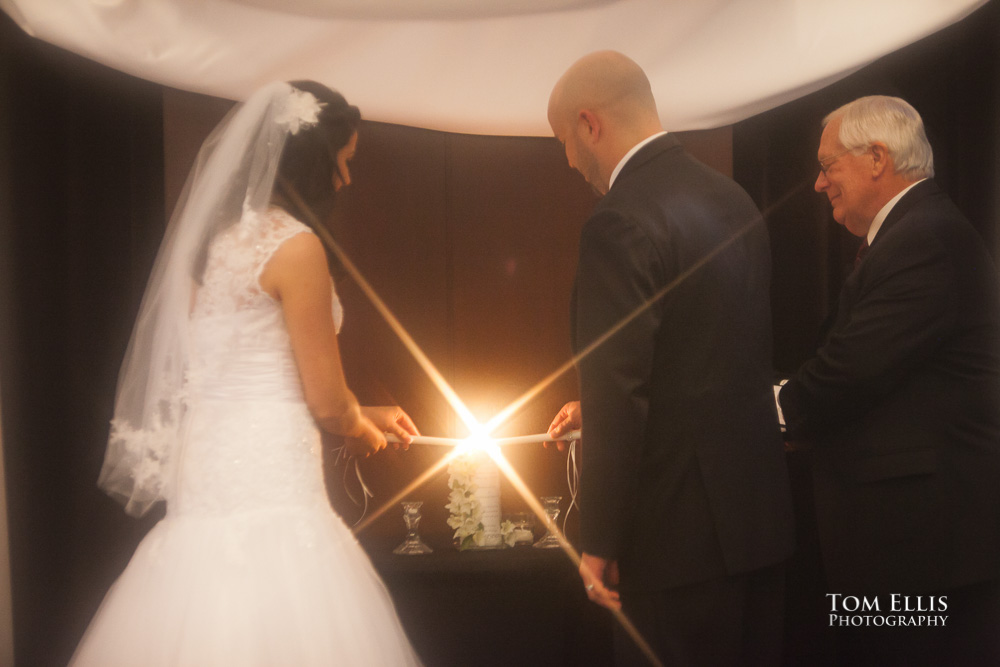 Bride and groom light their unity candle during their wedding ceremony at the W Hotel in Seattle
