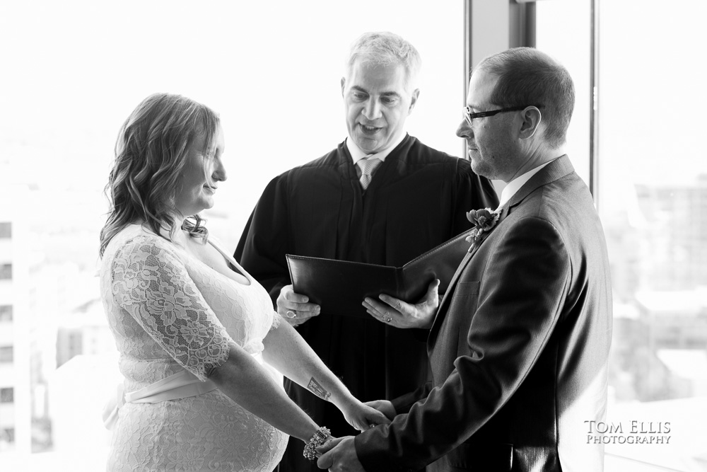 Bride and groom hold hands during their wedding ceremony at the Seattle Municipal Courthouse