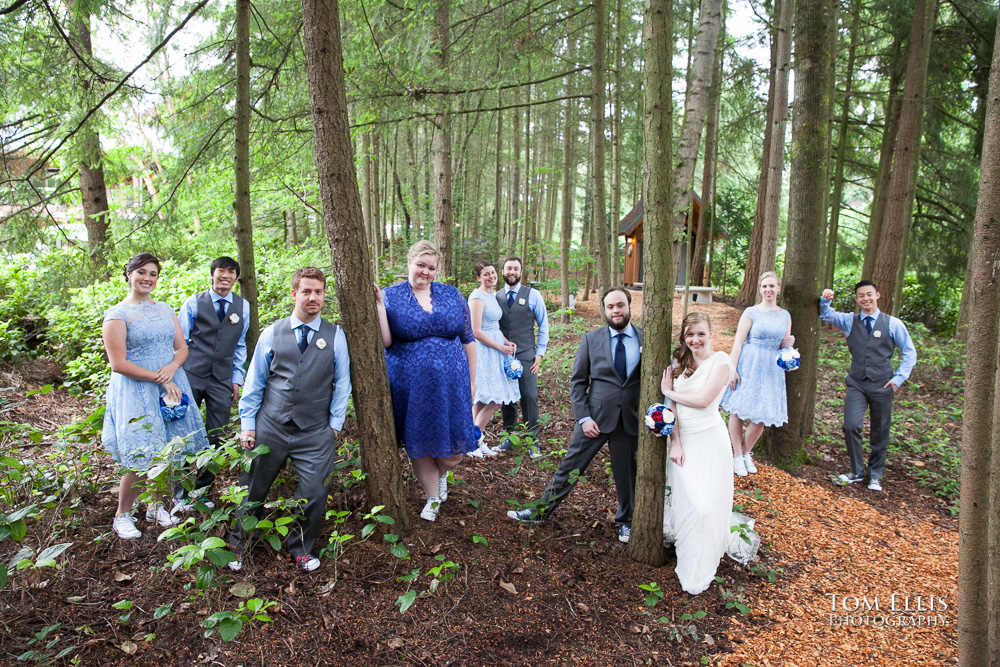 Bride, groom and their wedding party pose for a photo in the forest