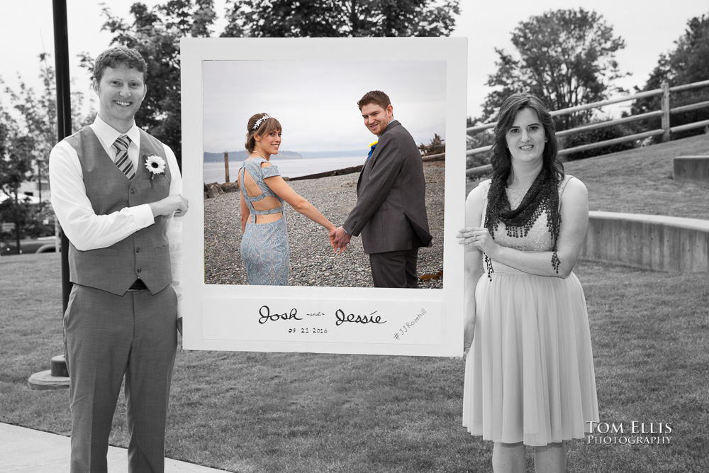 Black and white photo of Best Man and Maid of Honor holding picture frame containing a color photo of the bride and groom