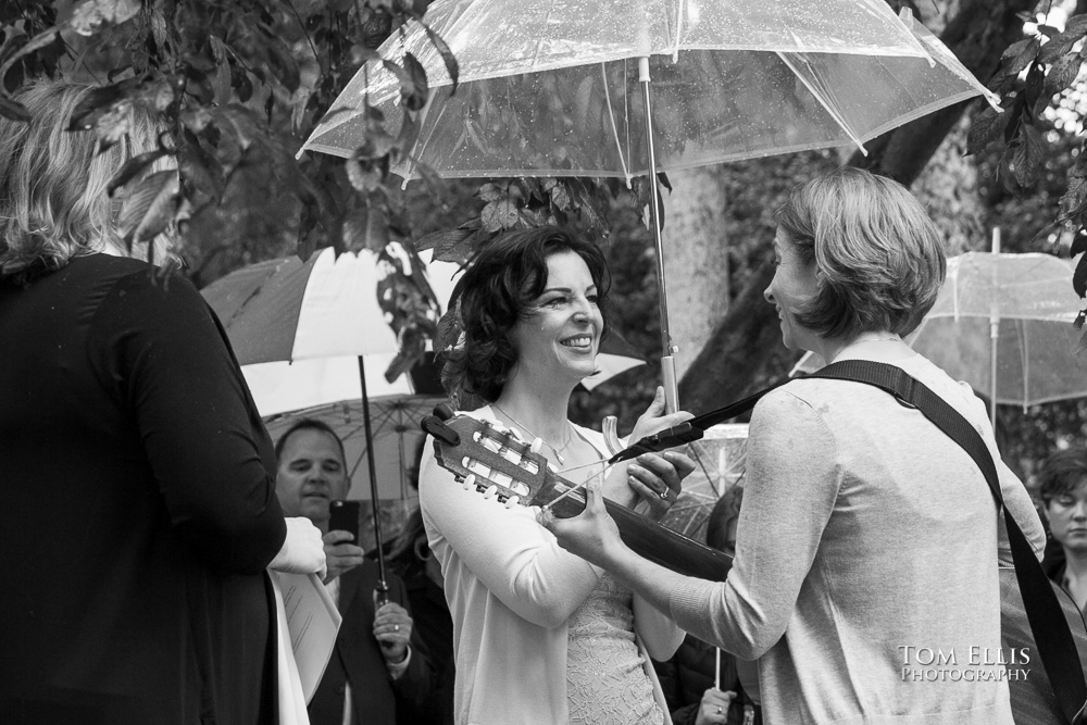 Black and white wedding photo of lesbian wedding ceremony as bride Sarah plays guitar and sings to bride Kelline