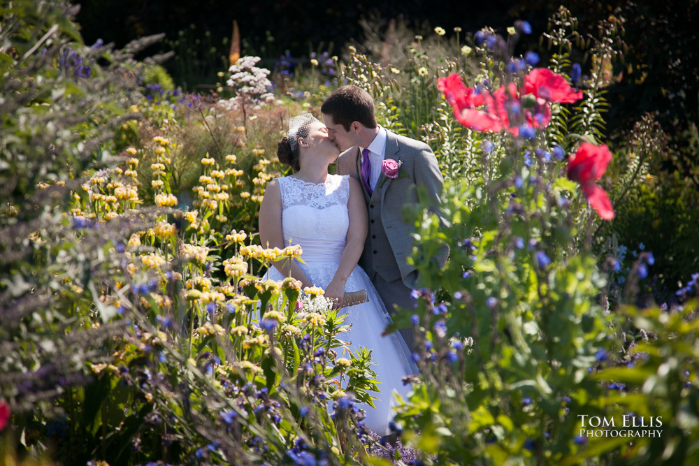 Bride and groom kiss in a beautiful flower garden