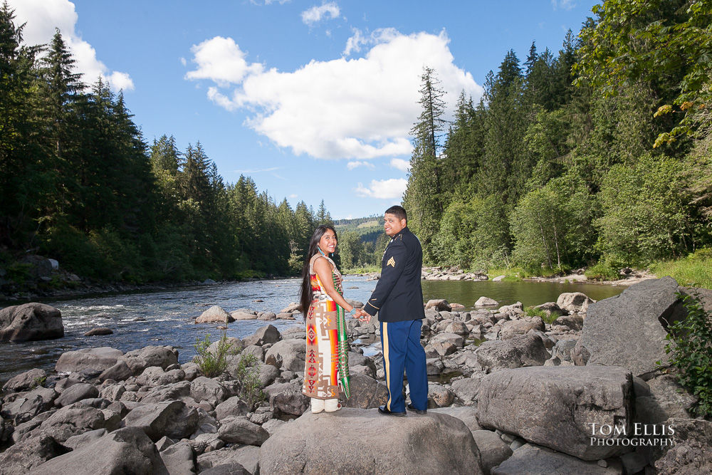 Man in dress military uniform with woman in Native American costume stand on large rock along the side of the Snoqualmie River