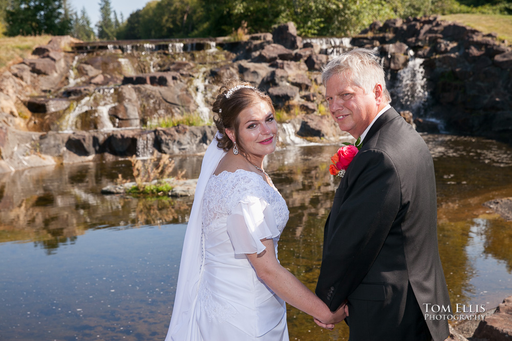 Bride and groom in front of the waterfall and pond at Echo Falls Golf Club