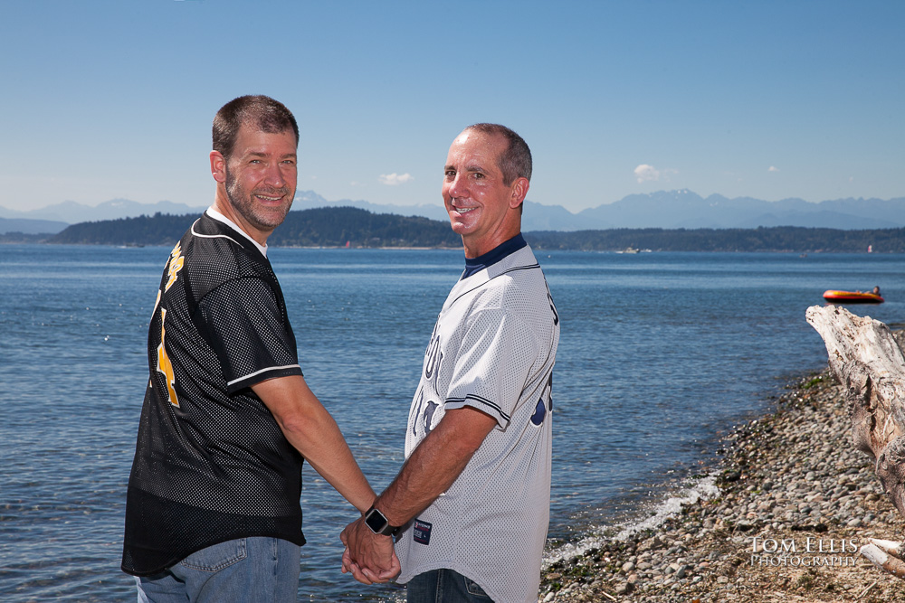 Gay couple walk hand in hand along beach, look back over shoulder at the camera