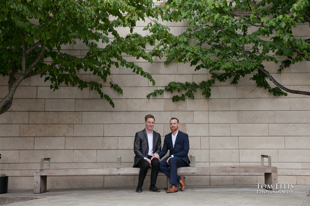 Newlywed gay couple sit together on a bench outside Seattle City Hall