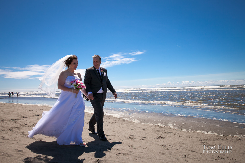 Bride and groom walk along the beach at Ocean Shores