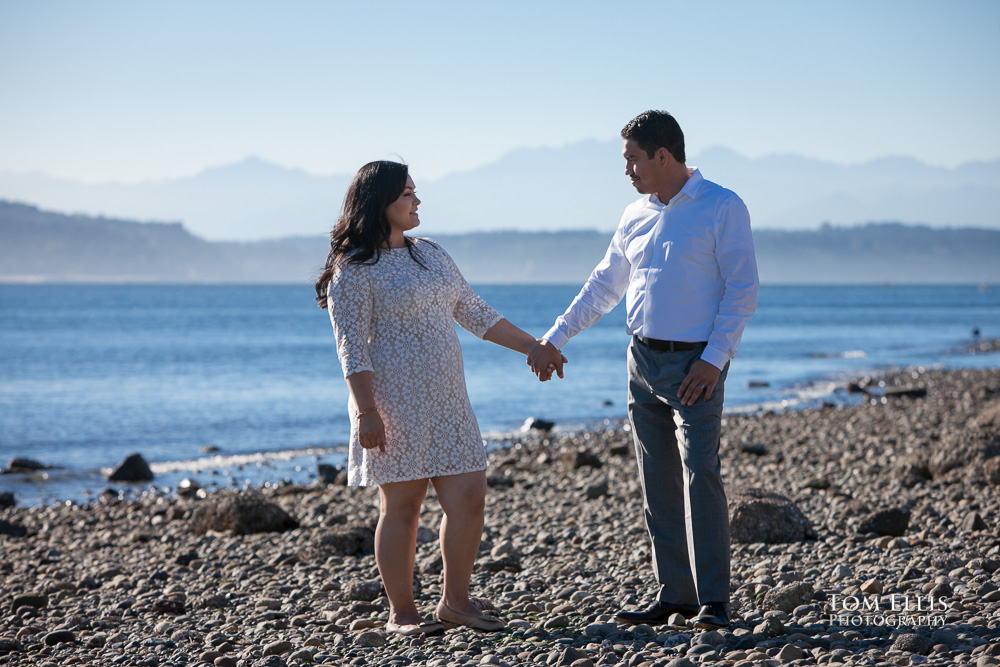 Couple standing hand-in-hand on beautiful beach, with view across Puget Sound to the Olympic Mountains