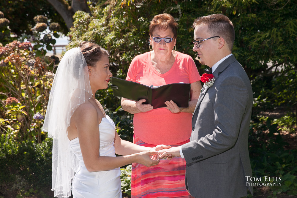 Couple standing with their wedding officiant in a beautiful park for their elopement