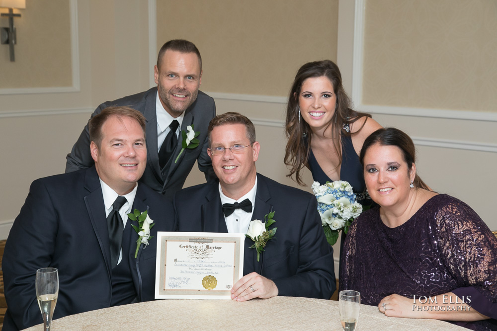 Gay couple and their witnesses and officiant show off their wedding certificate
