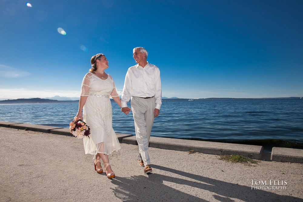 Bride and groom walk along the beachfront on Alki Point, with Puget Sound and the Olympic Mountains in the background