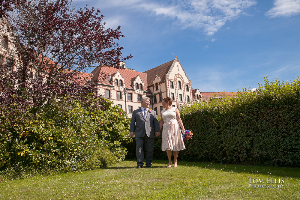 Bride and groom walk together in beautiful garden before their Seattle wedding ceremony