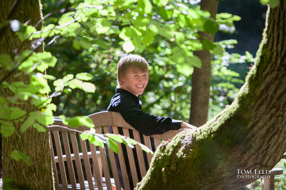 Senior boy sites on a bench surrounded by tress with beautiful backlighting highlighting him