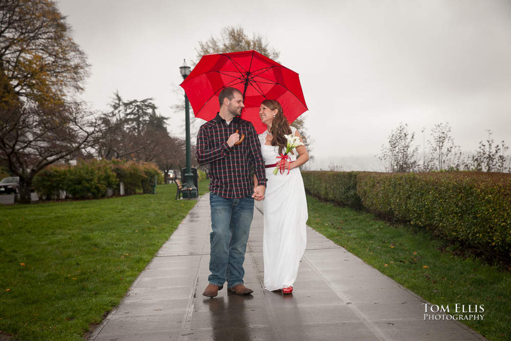 Couple walks under red umbrella before their Seattle area wedding ceremony in Grand Avenue Park