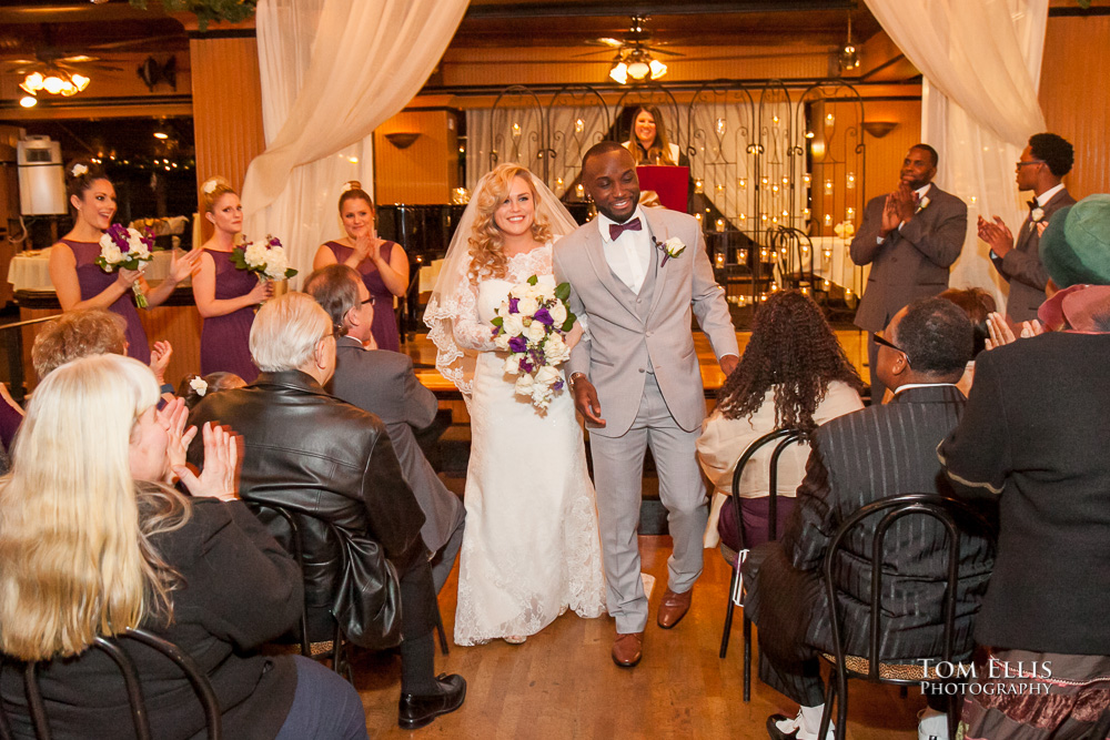 Bride and groom recess down the aisle at the conclusion of their Seattle wedding ceremony at the Lake Union Cafe
