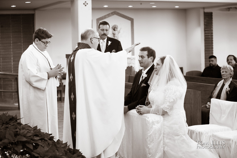 Sepia toned photo of wedding ceremony at Catholic church, as the priest blesses the kneeling couple just before pronouncing them married