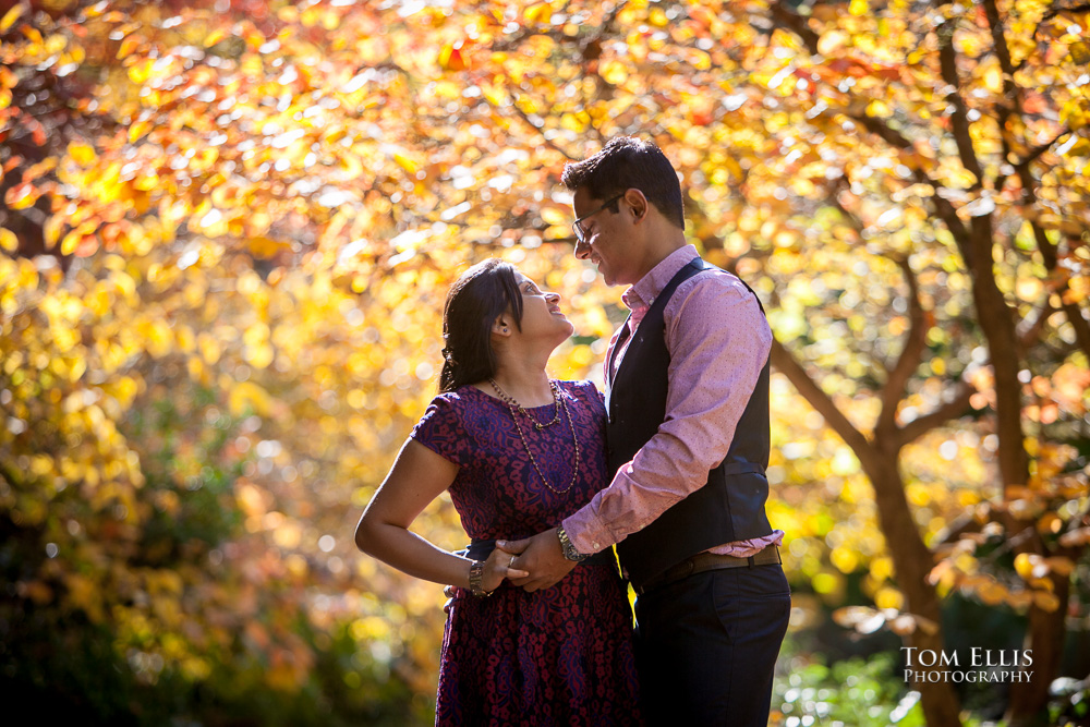 Couple poses against a background of brilliant yellow autumn foliage at the Washington Arboretum during their Seattle engagement photography session with Tom Ellis Photography