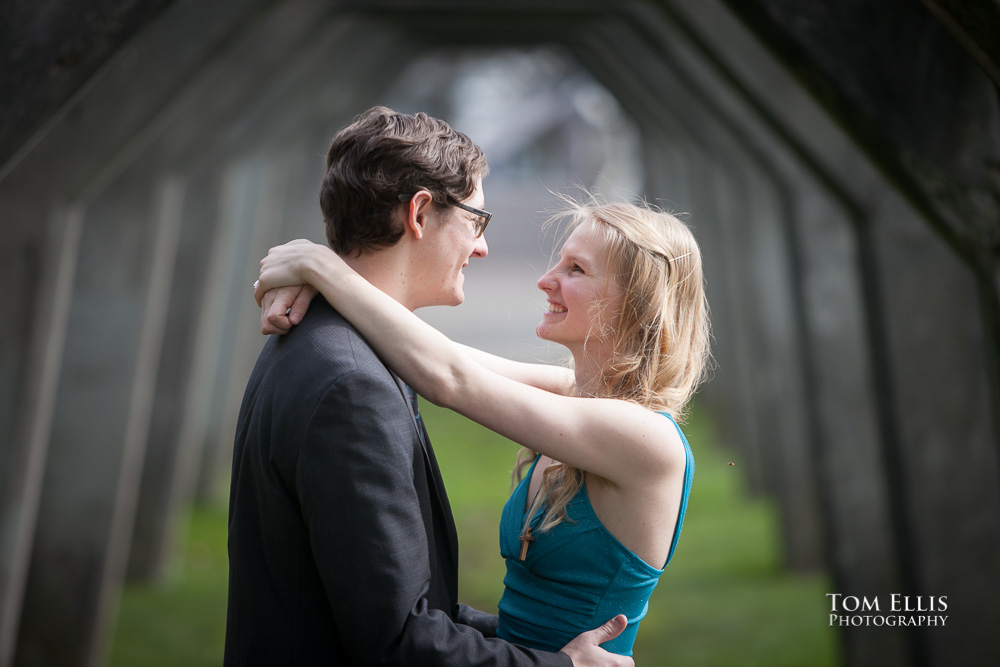Engagement photo of couple hugging under the old concrete arches at Gasworks Park in Seattle