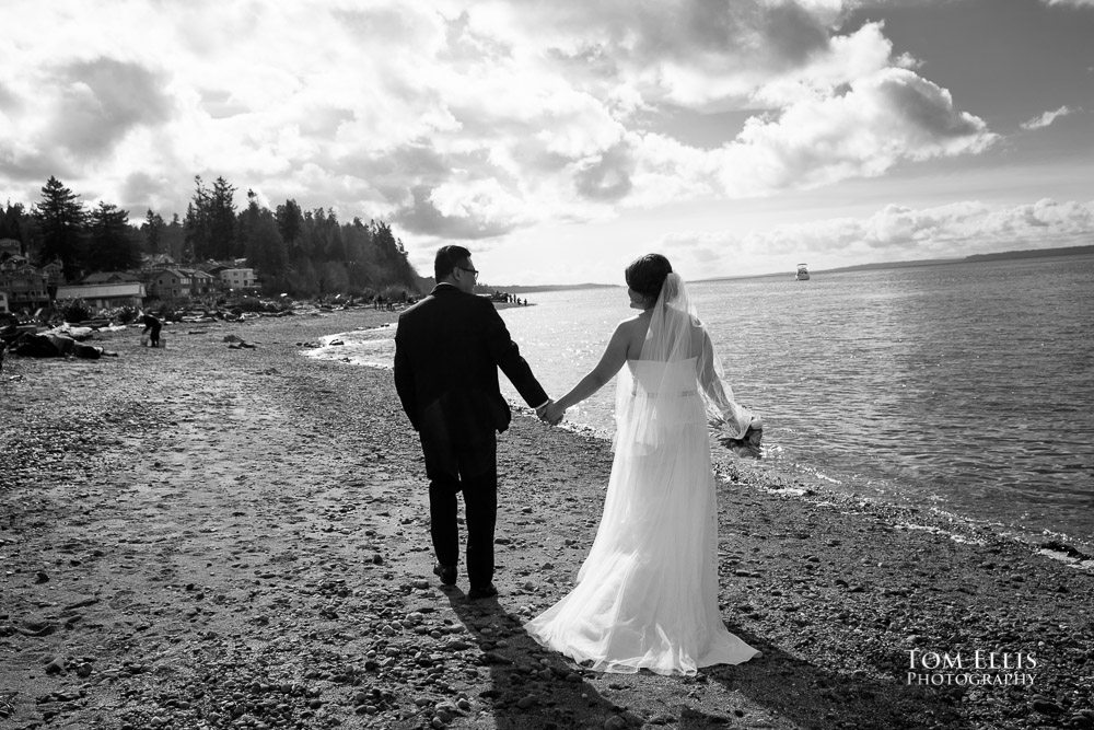 Romantic black and white photo of bride and groom walk along the beach in Mukilteo before their Seattle area wedding
