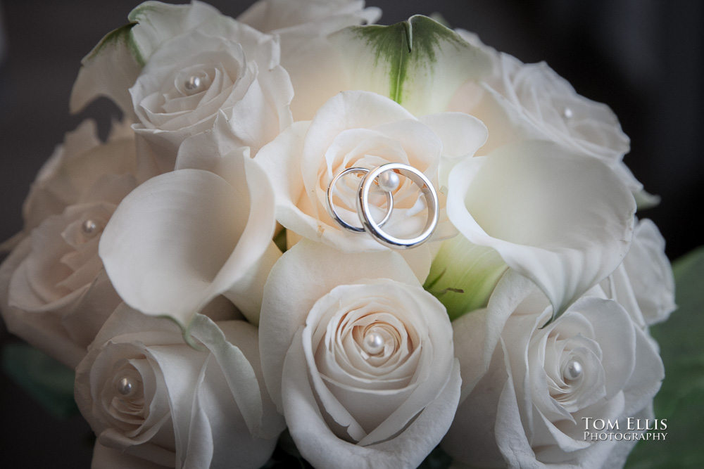 Close up photo of bridal bouquet with the bride's and groom's rings inside one of the flowers, at their wedding at the Seattle Municipal Courthouse