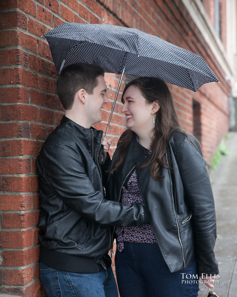 Engagement photo of couple standing under an umbrella against a brick wall in Seattle's Pike Place Market