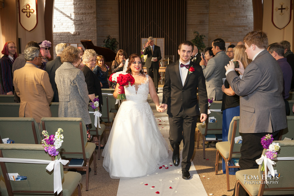 Bride and groom coming down the aisle at the conclusion of their Seattle wedding by Tom Ellis Photography