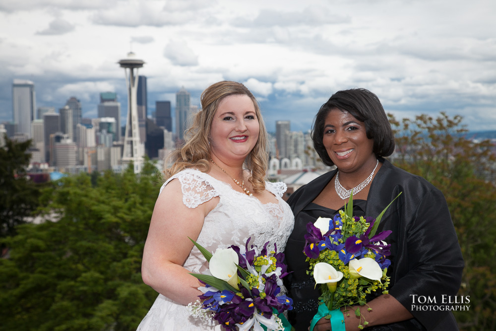 Two brides pose for photo at Seattle's Kerry Park, with the Space Needle in the background