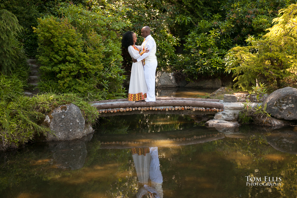 Couple dressed in traditional Ethiopian wedding costumes share a hug on one of the bridges at Seattle's Kubota Gardens during their wedding portrait session