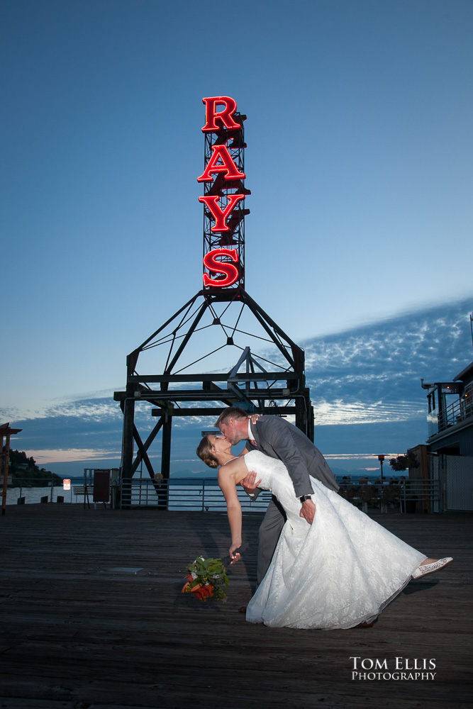 Groom dips his bride for a sunset kiss in front of the iconic neon sign at Ray's Boathouse in Seattle