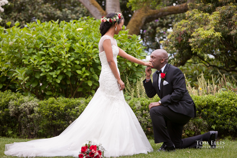 Groom kneels in front of his bride and kisses her hand
