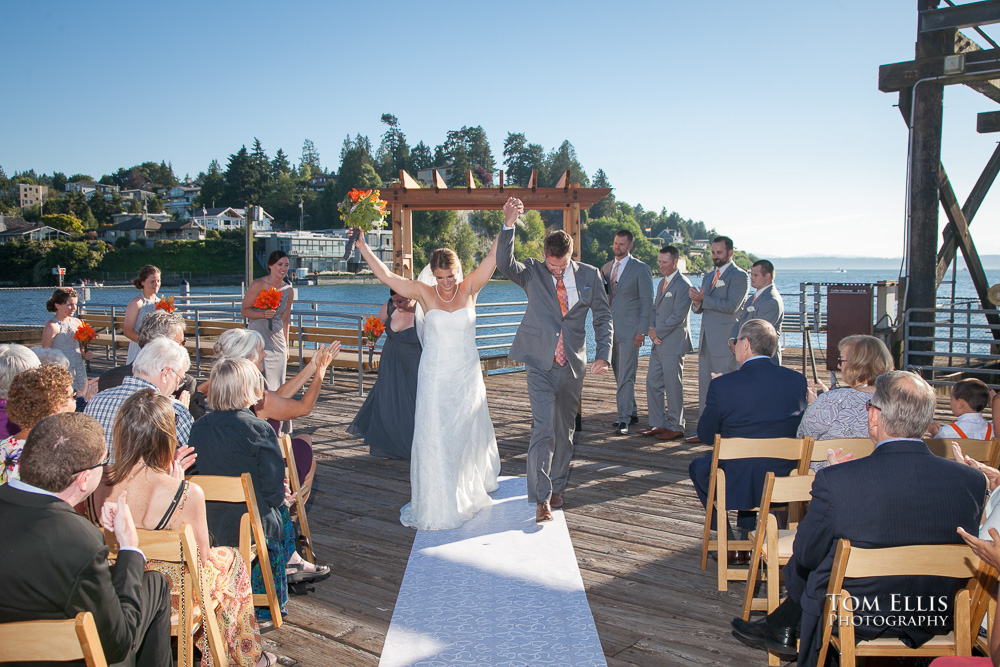 Bride and groom raise their hands over their heads in triumph as they recess down the aisle at the conclusion of their wedding ceremony at Ray's in Seattle