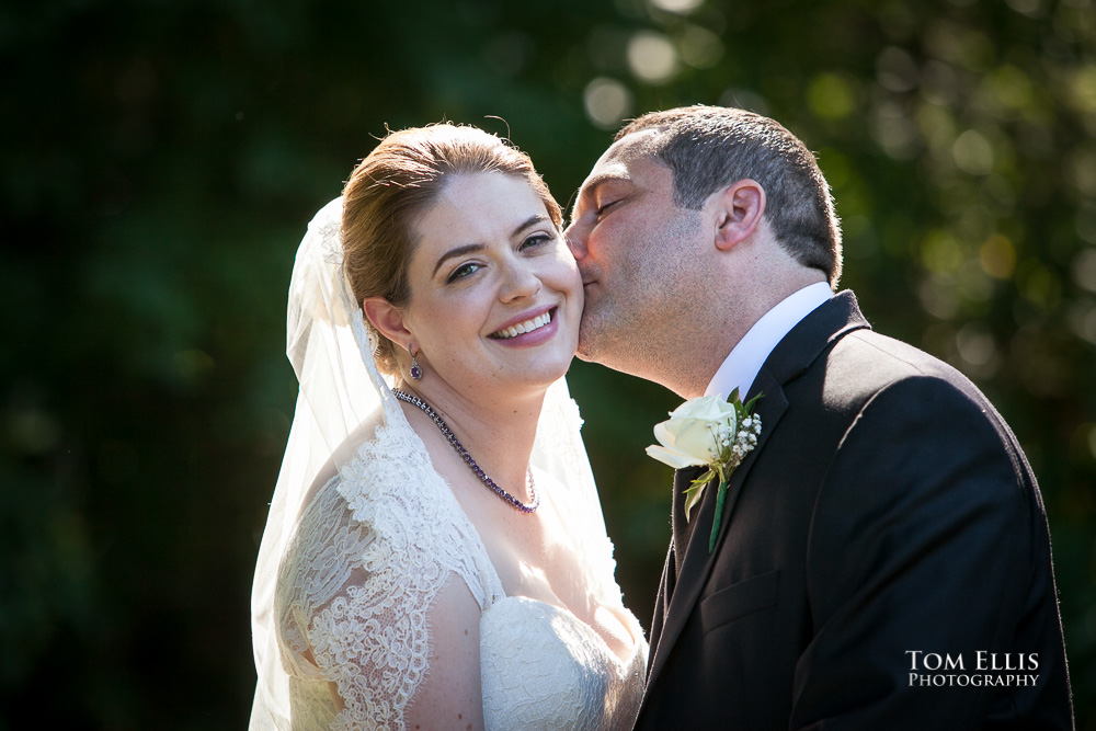 Groom gives bride a kiss on the cheek before their wedding at Tibbett's Creek Manor