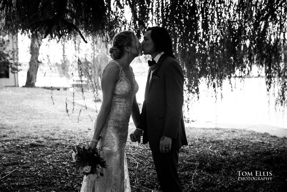 Black and white photo, silhouette of bride and groom kissing under a willow tree