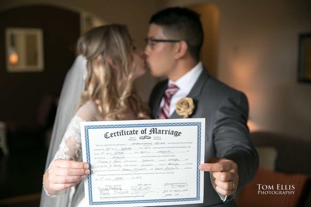 Bride and groom kiss while holding their marriage certificate up for the camera
