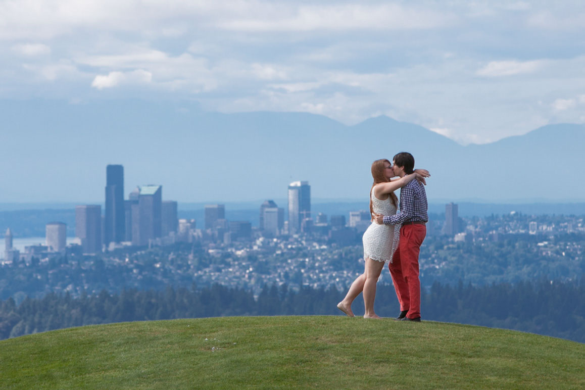 Couple kissing on hilltop with Seattle skyline and Olympic Mountains in the background, taken from Newcastle Golf Club during their Seattle area engagement photo session