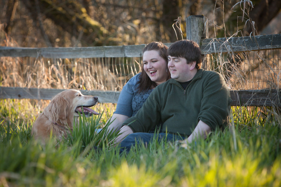 Seattle area engagement photo of couple with their Golden Retriever, sitting in the grass at Marymoor Park