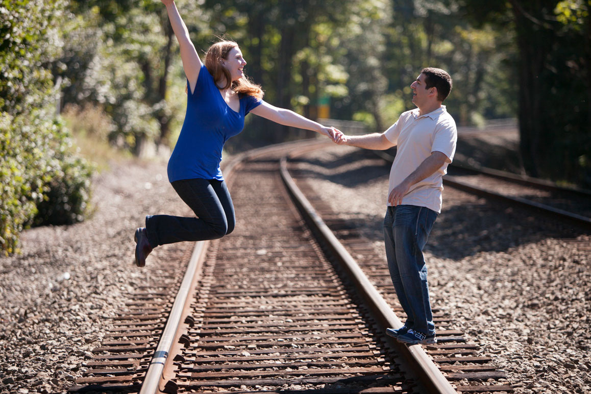 Rachel & Brett having fun on the train tracks during their Seattle engagement photos at Golden Gardens
