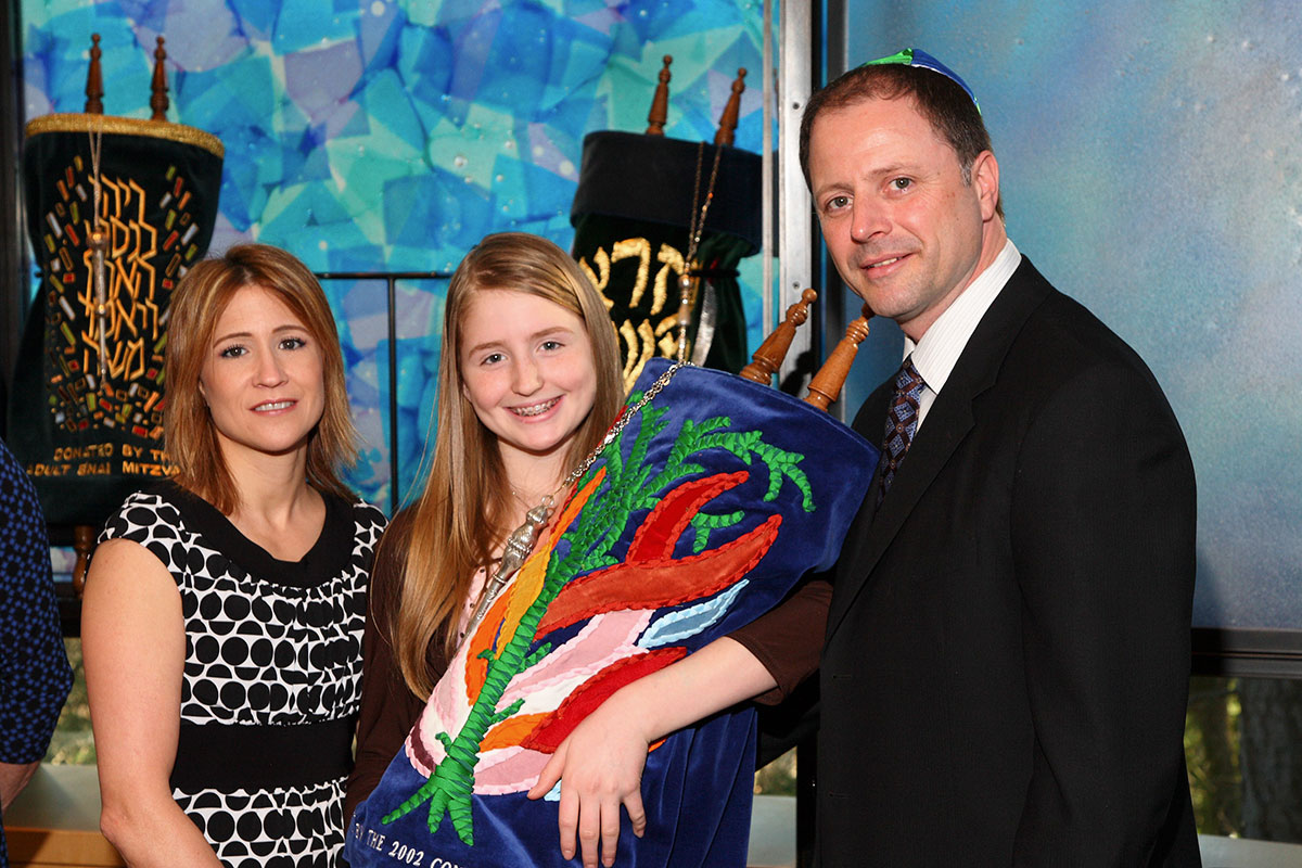 Rachel and parents with torah at Bellevue Bar Mitzvah at Temple de Hirsh Sinai