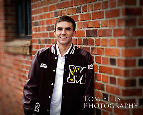 Senior boy in letterman's jacket leaning against old brick building at Luther Burbank Park
